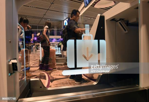 Passengers checkin their luggage using an automated booth at the newlyopened Changi International Airport's Terminal 4 in Singapore on October 31...