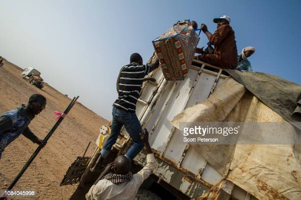 Passengers climb aboard a truck as it joins a convoy protected by military escort crossing the Sahara Desert from Niger north to Libya, often with...