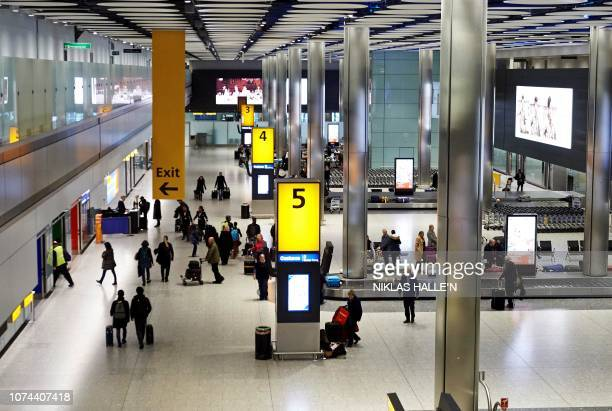 Passengers collect their luggage from the baggage reclaim area of Terminal 5 at London Heathrow Airport in west London on December 19 2018 Britain...