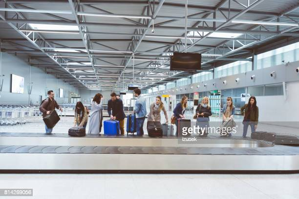 passengers collecting baggage from luggage conveyor belt at airport - baggage claim stock pictures, royalty-free photos & images