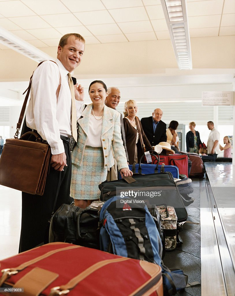 Passengers Collecting Luggage at an Airport Baggage Collection : Stock Photo