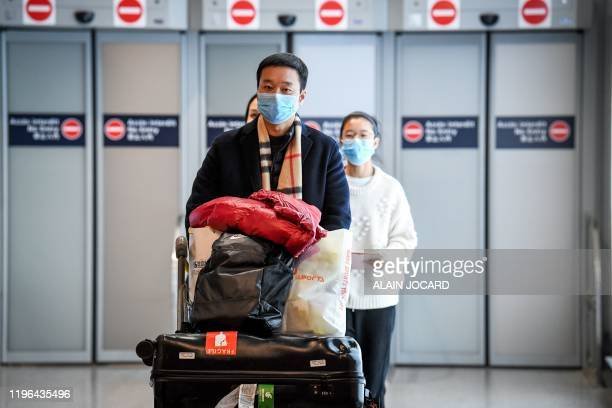 Passengers coming from China, leave the Terminal wearing paper masks after landing in Charles De Gaulle Airport on January 26, 2020 in...