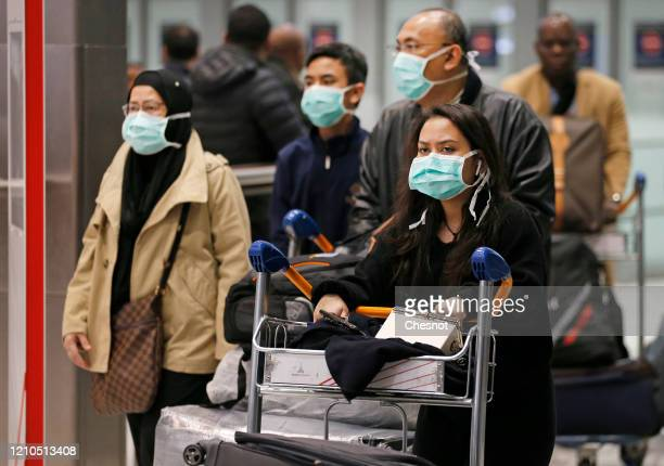 Passengers coming from China wearing protective masks leave the terminal 2 after landing at Roissy Charles de Gaulle airport on March 5 2020 in...