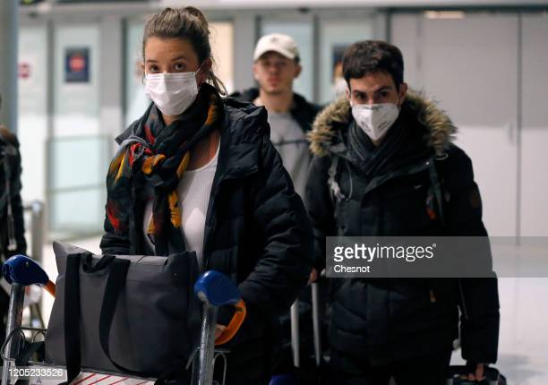 Passengers coming from China wearing protective masks leave the terminal after landing in Charles De Gaulle Airport on February 10 2020 in...