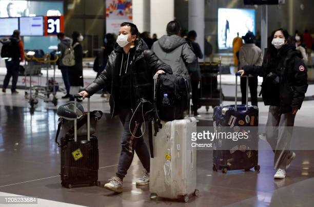 Passengers coming from China wearing protective masks leave the Terminal after landing in Charles De Gaulle Airport on February 10, 2020 in...