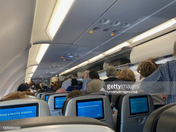 Passengers deplaning with Keep Health Distance message on monitors, JFK Airport, New York.