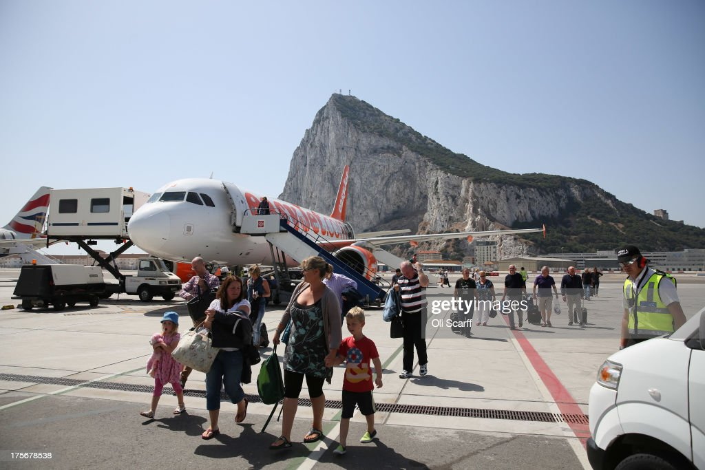 Passengers disembark a flight shortly after landing at Gibraltar International Airport on August 6, 2013 in Gibraltar. Tensions between the British and Spanish governments have been raised on issues surrounding the sovereignty of Gibraltar. An increase in Spanish border crossing checks between the Rock and mainland Spain, leading to lengthy queues, is widely considered to be a retaliatory move for the construction of an artificial reef in British waters, which it is claimed has had a negative impact on Spanish fishing vessels in the area.