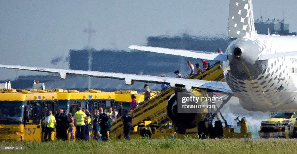 Passengers disembark a plane of the Spanish company Vueling after it landed at Schiphol Airport in Amsterdam on August 29, 2012. Dutch police and an airline dismissed reports today of a possible hijacking on a flight from Spain to Amsterdam, saying the alert was triggered by a 'miscommunication.' Dutch authorities went on high alert earlier, scrambling two Dutch F-16 fighter planes after the Vueling flight with 180 passangers on board from Malaga in Spain entered Dutch airspace without making radio contact.