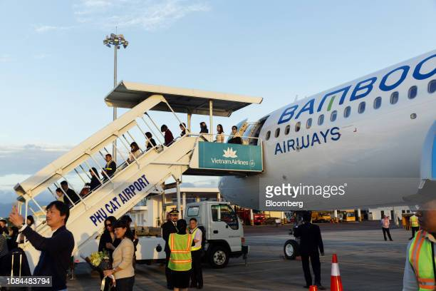 Passengers disembark an Airbus SE A321 Neo aircraft operated by FLC Group JSC's Bamboo Airways on the first day of the airline's operations at Phu...