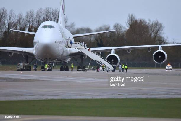 Passengers disembark from a plane carrying 150 Britons who were trapped in Wuhan following a Coronavirus outbreak after landing at RAF Brize Norton...