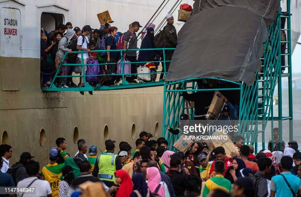 Passengers disembark from a ship at a seaport in Surabaya Indonesia's East Java province on May 31 as people travel to their hometowns ahead of Eid...