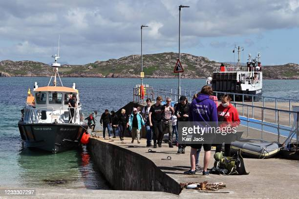 Passengers disembark from a sightseeing cruise as the ferry from Mull approaches the slipway on Iona, on June 6, 2021 in Iona, Scotland. The Scottish...