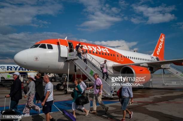 Passengers disembark from an Airbus A320 aircraft owned by British low cost carrier EasyJet at Schoenefeld airport near Berlin on July 13 2019