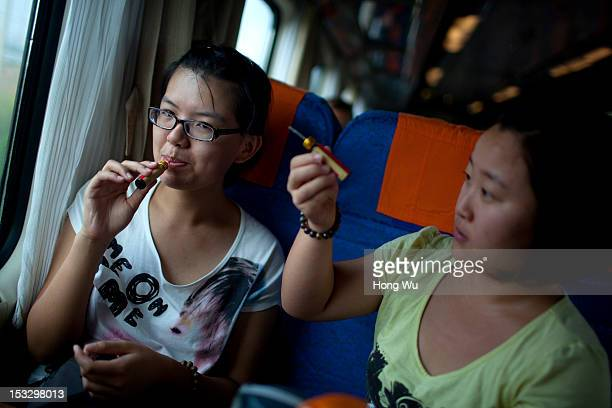 Passengers drink medicines preventing altitude stress in a train carriage of from Beijing to Lhasa on August 14 2012 in Zhongwei China After...