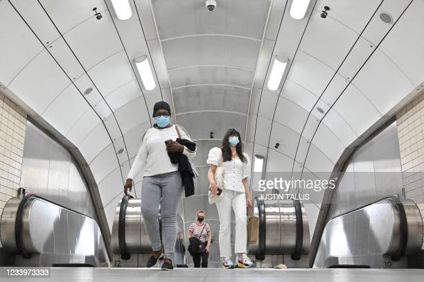 Passengers emerge from the London Underground in central London on July 14, 2021. - London Mayor Sadiq Khan called for use of face coverings to...