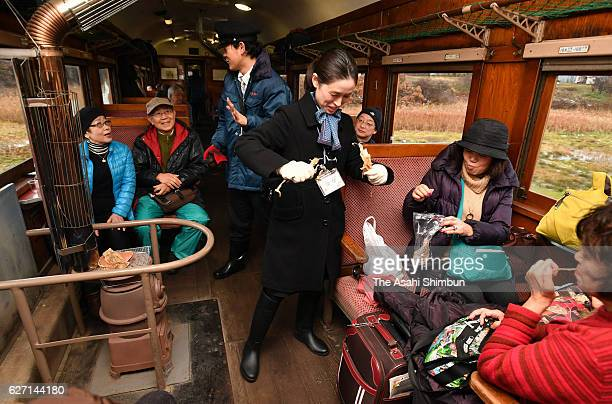 Passengers enjoy sake and grilled 'surume' dried squid on a 'stove train' on December 1 2016 in Goshogawara Aomori Japan On Tsugaru Railway Co's...