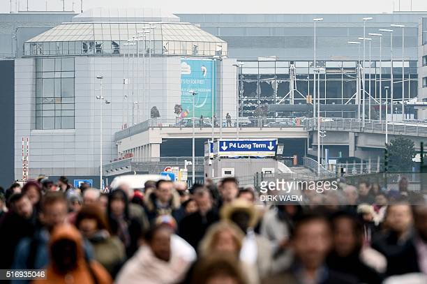 TOPSHOT Passengers evacuate the Brussels Airport in Zaventem on March 22 after a string of explosions rocked Brussels airport and a city metro...