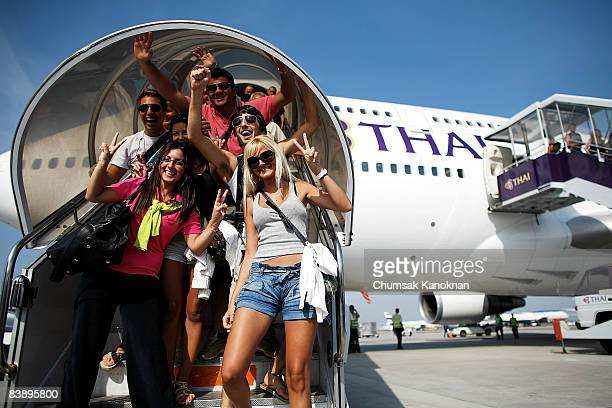 Passengers exit Thai Airways flight from Phuket the first to arrive after the end of the siege lands at Suvarnabhumi International Airport on...