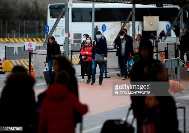 Passengers exit the port after disembarking with others from the Costa Smeralda cruise ship docked in the Civitavecchia port 70km north of Rome early...