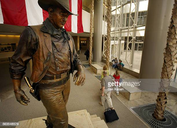 Passengers file by the statue of John Wayne at John Wayne Airport There s a proposal floating around to change the name of John Wayne Airport to the...