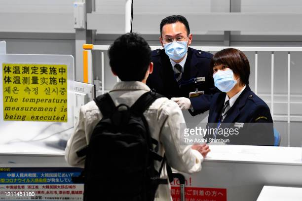 Passengers fill in a questionnaire at the quarantine counter of Kansai International Airport on March 9, 2020 in Izumisano, Osaka, Japan. Japan...
