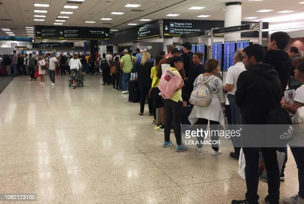 Passengers flying from Miami International Airport wait in line to enter the checkpoint at Concourse F where some of the flights of a closed terminal...