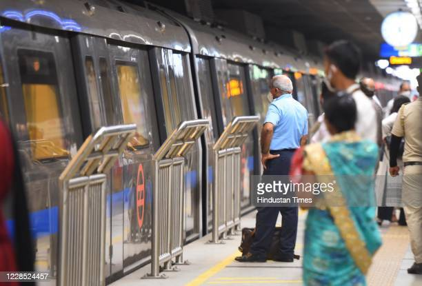 Passengers follow social distancing norms as they wait to enter a metro train after the metro resumed its services during Unlock 4 at Rajiv Chowk on...