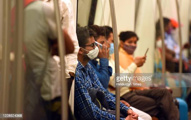 Passengers follow social distancing norms to prevent the spread of coronavirus while travelling in a metro train after the metro resumed its services...