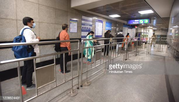 Passengers follow social distancing norms while waiting to enter Mandi House metro station after the metro resumed its services during Unlock 4 on...