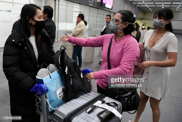 Passengers from a flight which originated in South Korea wear protective face masks upon landing at Mexico City's international airport on February...