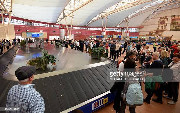 Passengers from a Germania Airline flight carrying 141 German tourists await for their luggage at the international airport of Egypt's Red Sea town...
