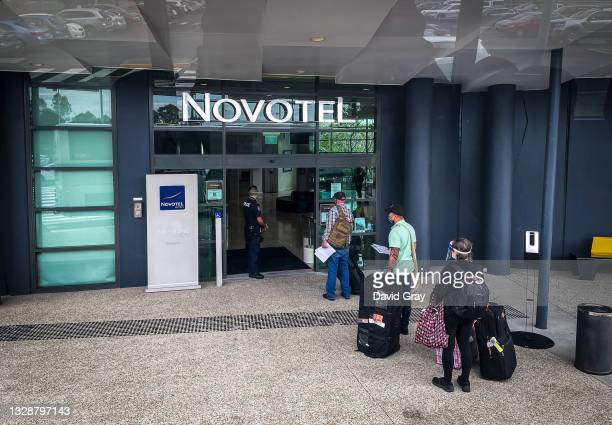 Passengers from an Air Niugini flight from Port Moresby wait to enter a hotel for their mandatory two-week quarantine on July 15, 2021 in Brisbane,...