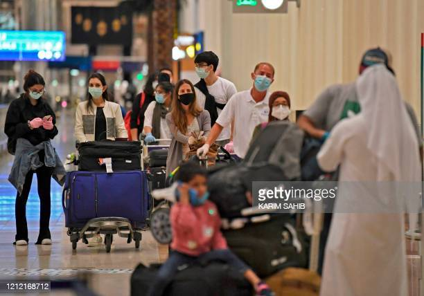 Passengers from an Emirates Airlines flight from London line up before being checked by health workers at Dubai International Airport on May 8 2020...