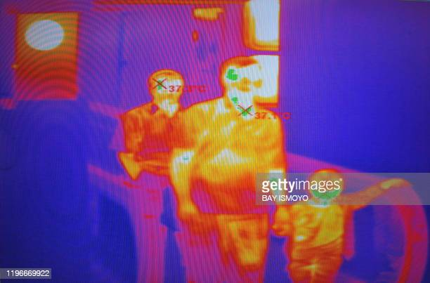 Passengers from an international flight are pictured on a thermal scanner monitor as they have their temperatures checked upon arrival at the...