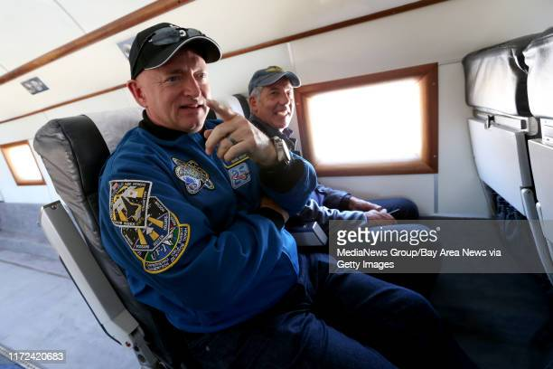 Passengers, from left, astronaut and naval aviator Mark Kelly and Rocky Moss ride aboard the Breitling DC-3 on a short flight above the San Francisco...