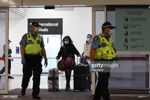 Passengers from Qantas flight QF583 are escorted to waiting Transperth buses by Police Officers after being processed following their arrival at...