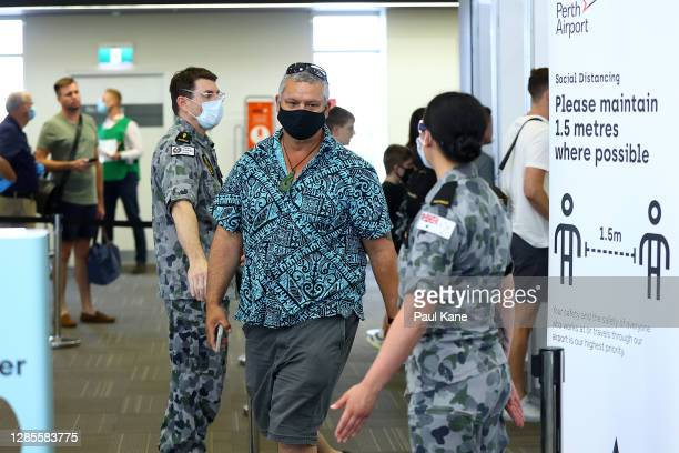 Passengers from Qantas flight QF937 from Brisbane walk from the processing area after being temperature tested and having their G2G pass verified by...