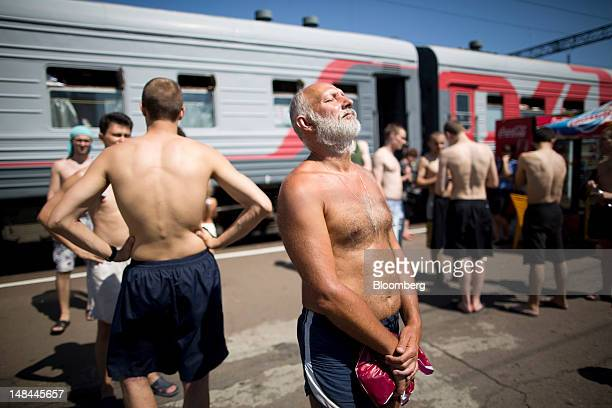 Passengers from the Novorossiysk-Moscow train, operated by OAO Russian Railways, sunbathe on a platform at Liski station in Voronezh region, Russia,...