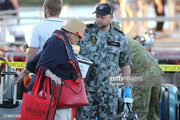 Passengers from the Vasco da Gama are assisted with their luggage by Australian Defence Force personnel after returning from quarantine on Rottnest...