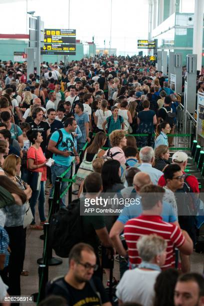 Passengers gather as they wait for passing the security controls at Barcelona's El Prat airport due to a strike of security agents on August 4 in...