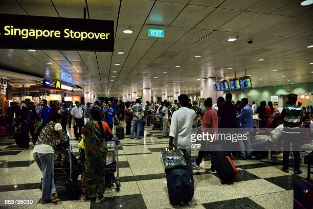 Passengers gather at Changi International Airport terminal 3 after being evacuated from terminal 2 due to a fire in Singapore on May 16 2017 Hundreds...