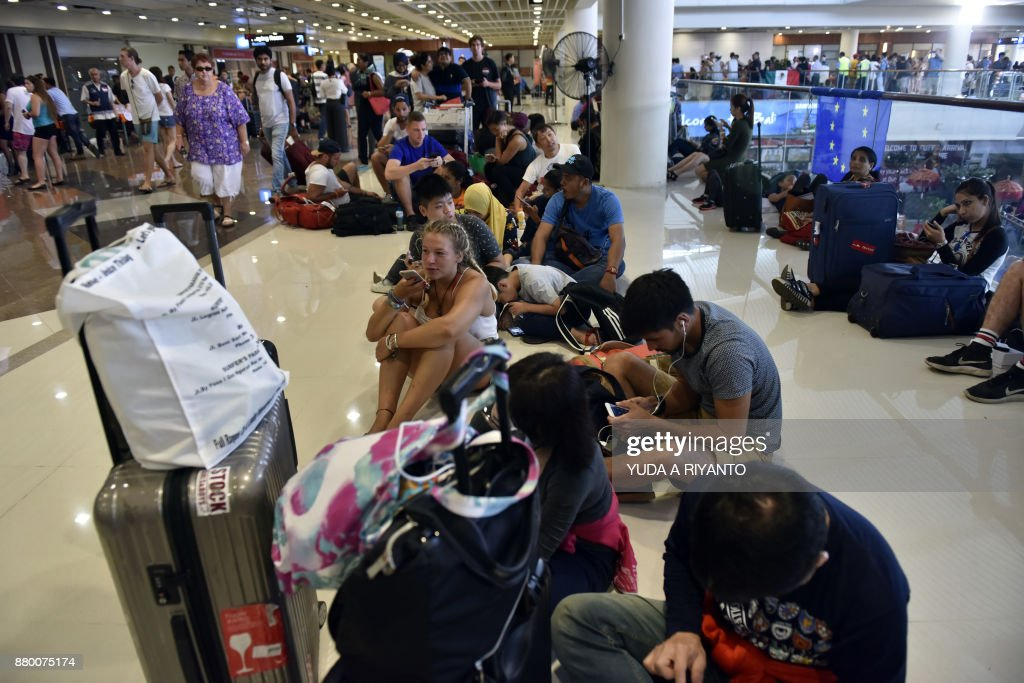 Passengers gather at the Gusti Ngurah Rai International airport in Denpasar, Bali on November 27, 2017, after flights were cancelled due to the threat of an eruption by the Mount Agung volcano. A rumbling volcano on Bali could erupt at any moment, authorities warned on November 27 as they raised alert levels to maximum, accelerated a mass evacuation and closed the main airport, leaving thousands of tourists stranded on the Indonesian resort island. / AFP PHOTO / Yuda A