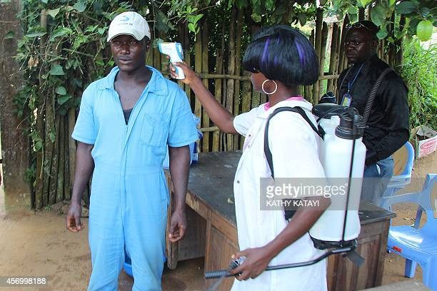 Passengers get their temperature measured as part of prophylactic measures against the spread of the Ebola virus upon their arrival at Boende's...