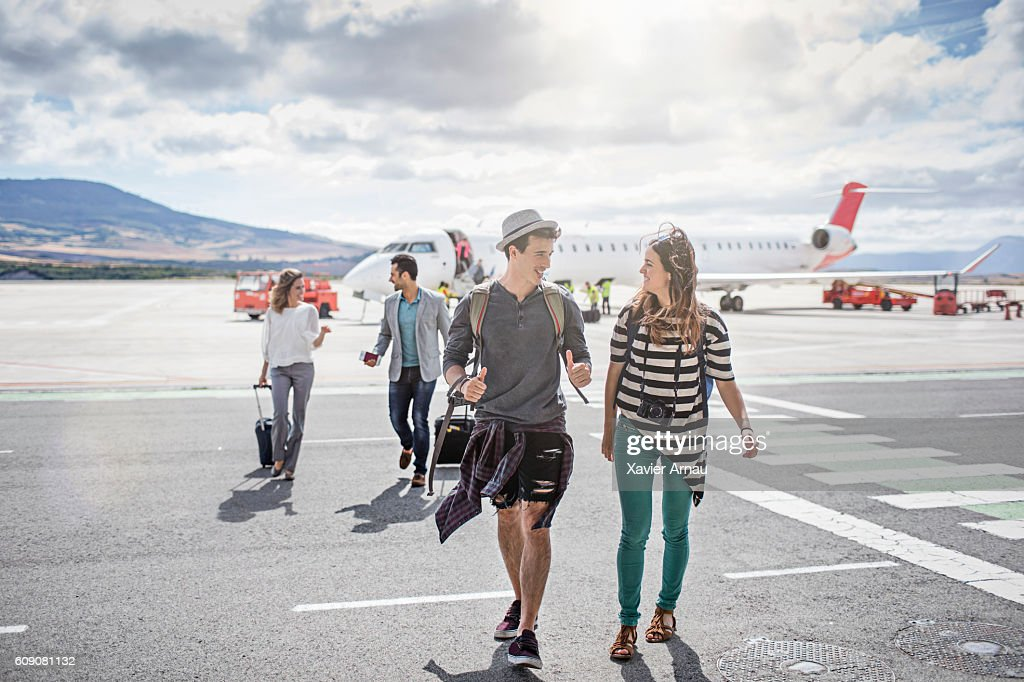 Passengers getting out of the airplane on a sunny day : Stock Photo