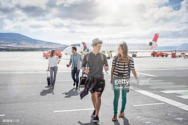 Passengers getting out of the airplane on a sunny day