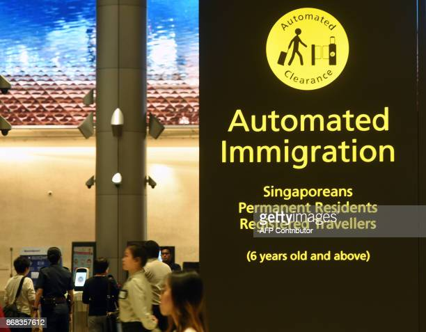 Passengers go through an automated immigration gates at the newlyopened Changi International Airport's Terminal 4 in Singapore on October 31 2017...