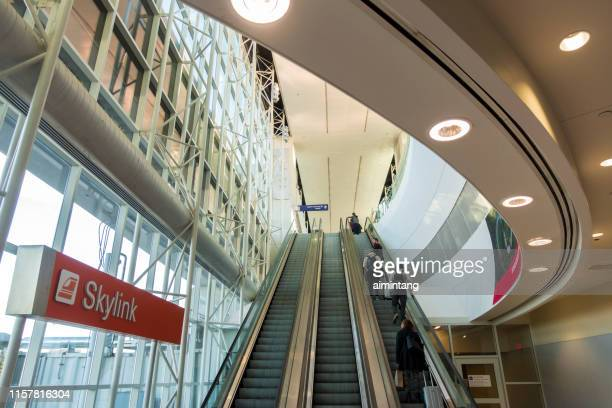 passengers going to the skylink train stop at dallas fort worth international airport - dallas fort worth airport stock pictures, royalty-free photos & images
