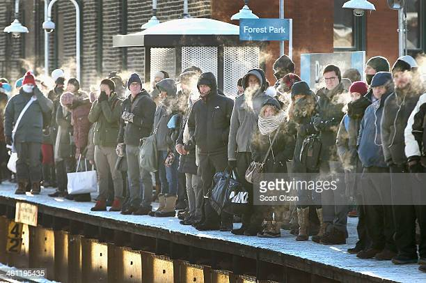 Passengers heading into downtown wait on an L platform for the train to arrive in below zero temperatures on January 7 2014 in Chicago Illinois...