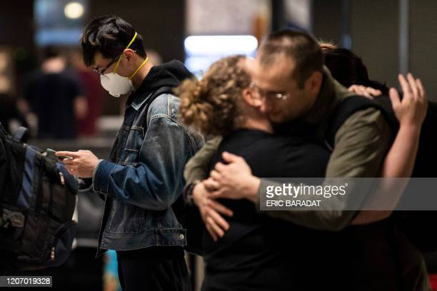 Passengers hug as a man wearing a mask to protect himself from the new coronavirus looks at his phone in the International arrivals zone at Dulles...
