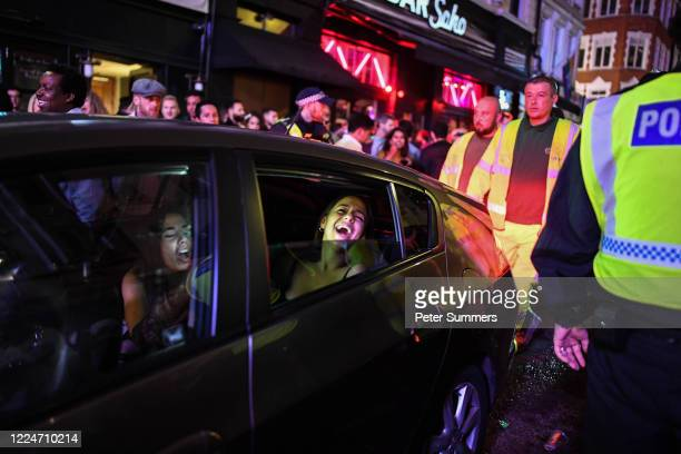 Passengers in a taxi are seen laughing as they drive through thick crowds in Soho on July 4 2020 in London United Kingdom The UK Government announced...